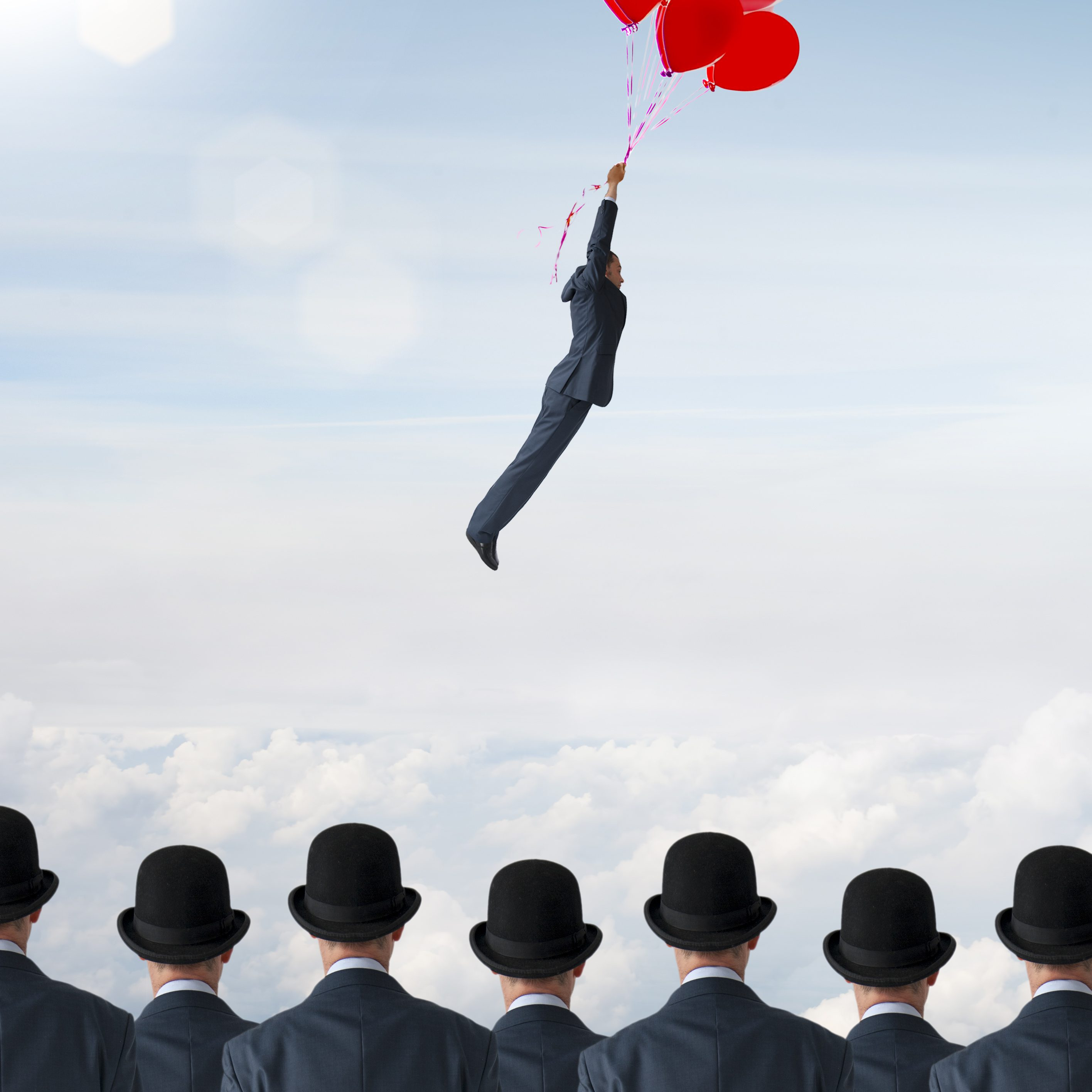 business individuality concept businessman flying away from crowd with balloons