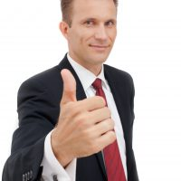 Portrait of young happy business man showing thumb's up sign. Approval, good work, and success.